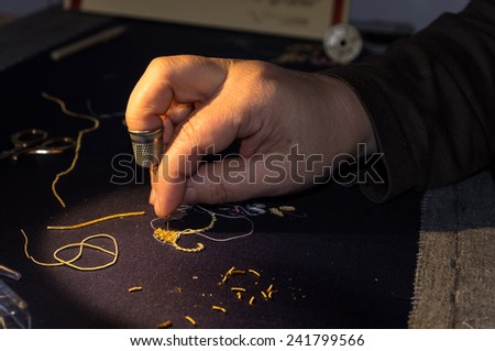a woman embroiders using the golden thread - stock photo