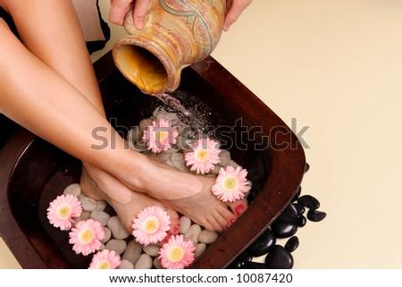A woman enjoys a soothing foot spa pedispa - stock photo