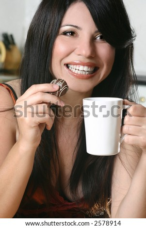 A woman enjoys coffee and chocolate - stock photo