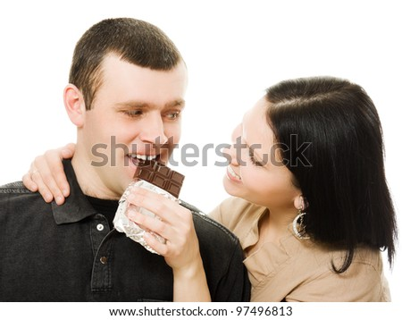 A woman feeding a man chocolate on a white background.