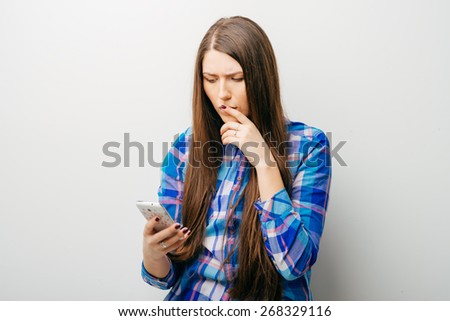 a woman gets bad news by text message and is shocked. - stock photo