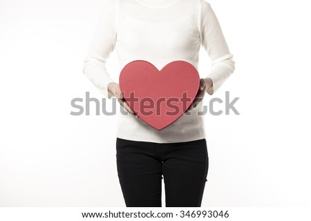 A woman(girl, female) wearing white sweater(shirts), black pants hand hold a red heart(love) gift box(package) isolated white at the studio. - stock photo