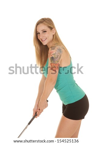 A woman golfer with a smile on her face, getting ready to putt. - stock photo