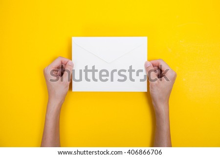 A woman hand hold a envelope and post card on yellow background - stock photo