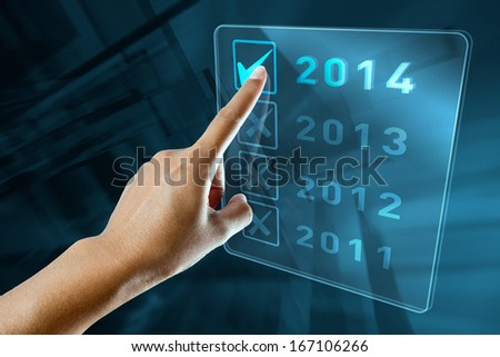 A woman hand selects 2014 on a digital screen
