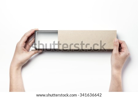 A woman hands hold a brown empty(blank, hollow, vacant) long paper box(case, package) and open on the white desk(table) top view isolated white at the studio. - stock photo