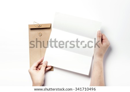 A woman hands hold a white(empty, blank, vacant, hollow) paper(letter, document) and a brown leather envelope top view isolated white at the studio. - stock photo