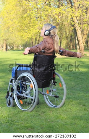 A Woman happy in a wheelchair with arms spread - stock photo