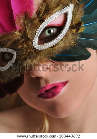A woman has a feather mask on with bright eyes and lips with makeup. Use it for a Halloween or glamor concept. - stock photo