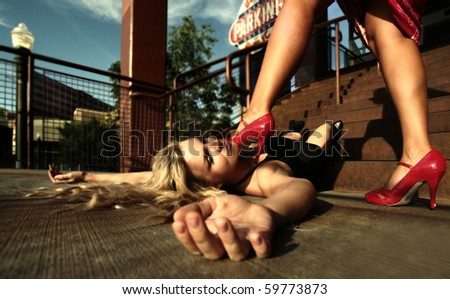 a woman has a foot on her rival on the stairs - stock photo