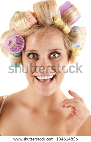 A woman has curlers in her hair and is smiling. - stock photo