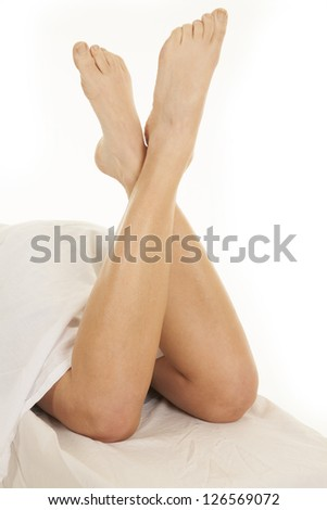 A woman has her legs coming out of a sheet on a bed. - stock photo