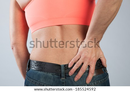 A woman has some dorsal pain and is touching her back.