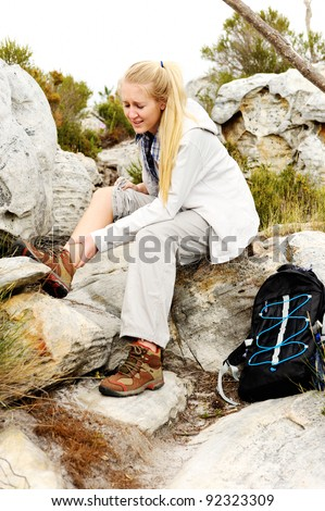 A woman has sprained her ankle while hiking - stock photo