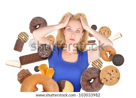 A woman has sweet food snacks around her on a white background. She has fear and there are donuts and cookies. Use it for a health or diet concept. - stock photo