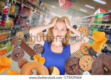 A woman has sweet food snacks around her on in a grocery store. She has fear and there are donuts and cookies. Use it for a health or diet concept.  - stock photo