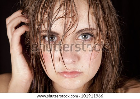 A woman has wet and sweaty hair and face. - stock photo