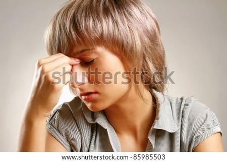 A woman having a headache, closeup - stock photo
