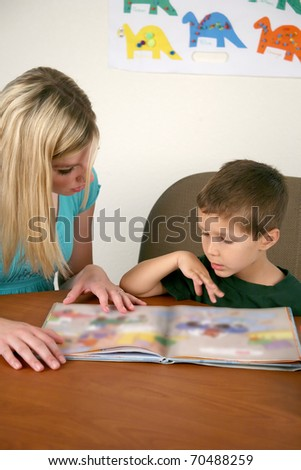 A woman helping a young child read a book - stock photo