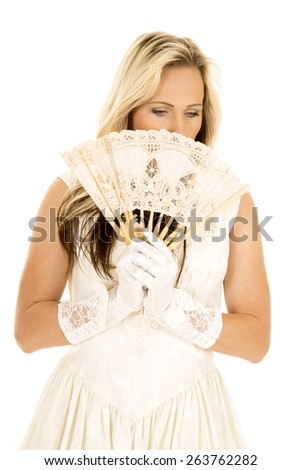 a woman hiding behind her fan, in her dress. - stock photo