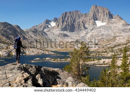 A Woman Hiker Stands High Above Garnett Lake in the Sierra Nevada. The Ansel Adams Wilderness, Sierra Nevada, California - stock photo