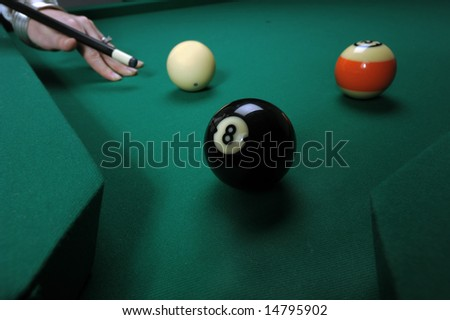 A woman hits balls on a pool (billiards) table during play
