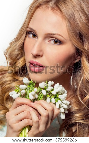 A woman holding a bouquet of snowdrops. Portrait of the blonde with flowers on a white background.