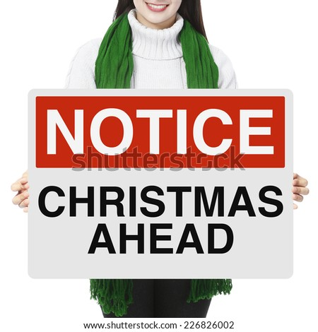 A woman holding a Christmas sign