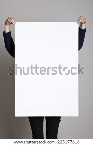 A woman holding a empty(blank) white paper poster or board. - stock photo