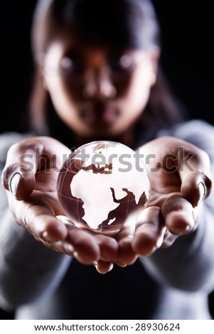 A woman holding a glass globe showing Africa. Europe and Middle East