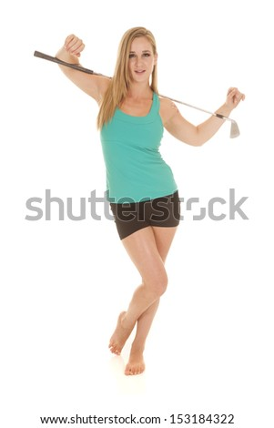 A woman holding a golf club on her shoulders. - stock photo