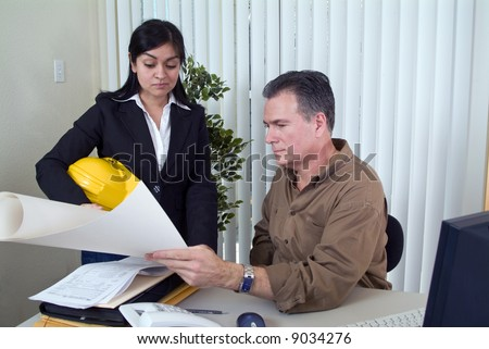 A woman holding a hardhat looking at what appears to be a set of plans held by a man. - stock photo