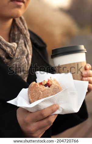 A Woman Holding a Jelly Donut and a Coffee on a Fall Day. - stock photo
