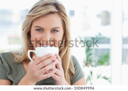 A woman holding a mug in her hands up to near her mouth, while smiling and looking in front of her. - stock photo