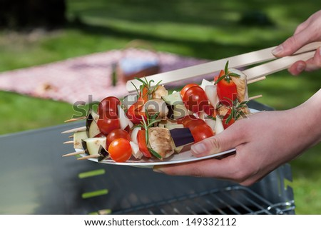 A woman holding a plate with vegetable sticks - stock photo