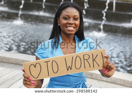 """A woman holding a sign saying """"love to work"""" in front of a fountain. - stock photo"""