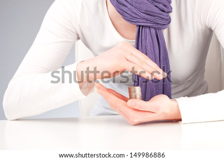 A woman holding and protecting a stack of coins. A conceptual image about savings, financial safety and security, investments or banking. - stock photo
