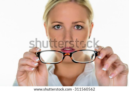 a woman holding glasses in hand. symbolic photo for poor vision and refractive error - stock photo