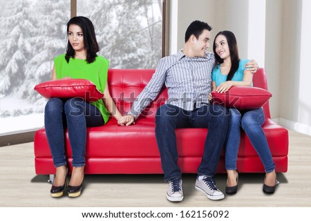 A woman holding hand with man sitting near his girlfriend - stock photo