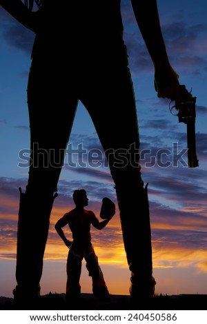 A woman holding on to a pistol, with a cowboy in between her legs. - stock photo