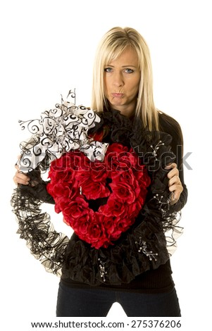 a woman holding on to her heart wreath with a sad expression on her face. - stock photo