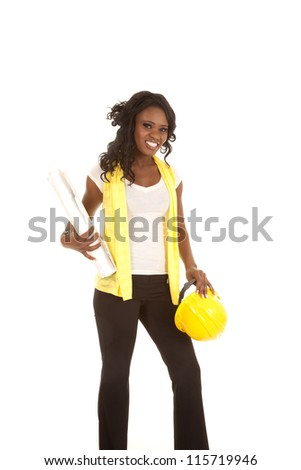 a woman holding on to her yellow hard hat and her blue prints with a smile on her face - stock photo