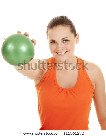 a woman holding out her green weighted ball with a smile on her face. - stock photo