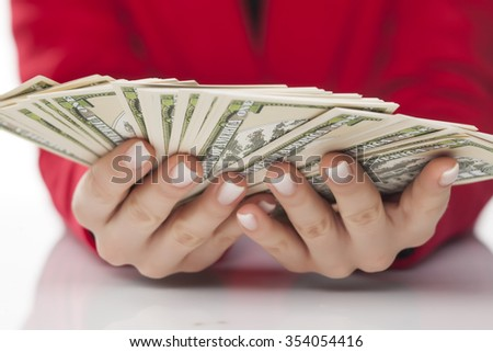 A woman holds a bunch of dollars