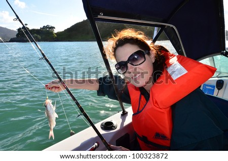A woman holds a fish that she caught during fishing at sea on a fishing boat. - stock photo