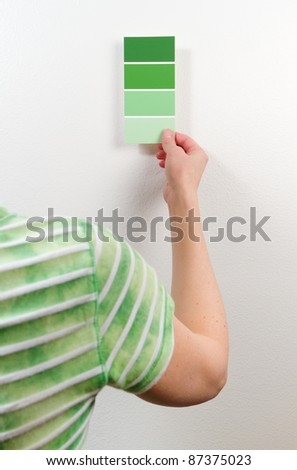 A woman holds a paint swatch card near a wall to compare the green shades. - stock photo