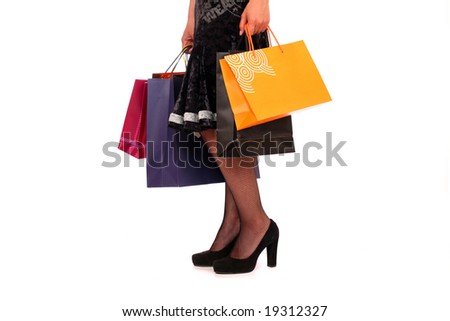A woman holds bags in her hands, standing on white background.