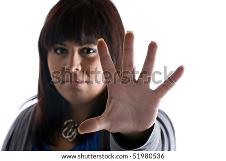 A woman holds up the palm of her hand in a defensive manner.  Great conceptual image for spousal abuse or bullying victims. Shallow depth of field. - stock photo