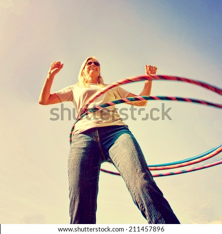 a woman hula hooping on a clear day toned with a retro vintage instagram filter - stock photo