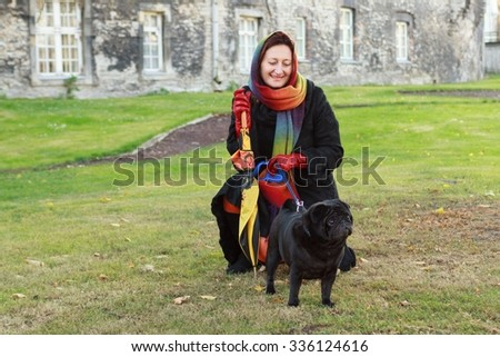 A woman in a black coat and a bright scarf on her head, on a walk in the autumn park , selective focus